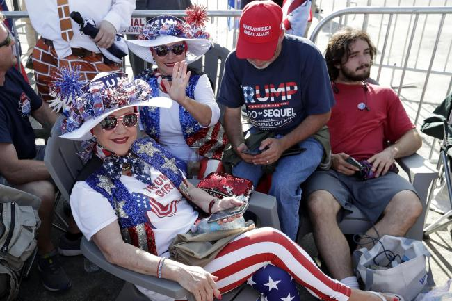 Supporters of President Donald Trump wait in line hours before the arena doors open for a campaign rally in Orlando, Florida