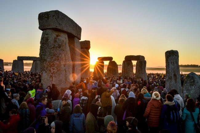 The sun rises between the stones and over crowds at Stonehenge where people gather to celebrate the dawn of the longest day in the UK. PRESS ASSOCIATION Photo. Picture date: Friday June 21, 2019. The neolithic Wiltshire monument is built along the solstic