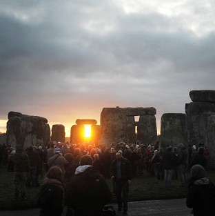 People watch the sunrise during the winter solstice celebration at Stonehenge