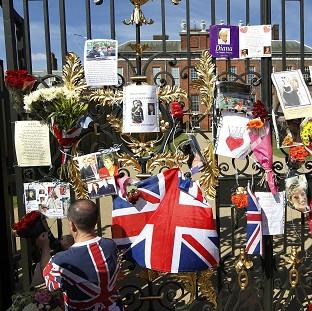 A man places a floral tribute for Diana, Princess of Wales on the gate of Kensington Palace in London (AP)
