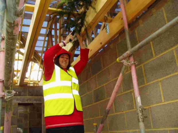 Cllr Toni Coombs wields a hammer to 'Top Out' Acorn Lodge at Oakdene Care Home in Three Legged Cross.