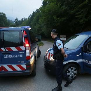 Gendarmes block access to a killing site near Chevaline, in the French Alps (AP)