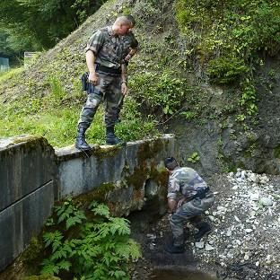 Salisbury Journal: French police inspect a drain under the road to the murder scene at Cheverlaine near Annecy