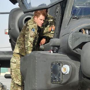 Prince Harry examining the cockpit of an Apache helicopter at Camp Bastion in Afghanistan (PA/MoD)