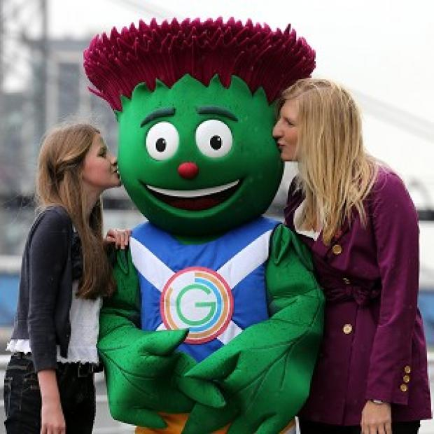 Glasgow Commonwealth Games mascot Clyde is kissed by his designer 12-year-old Beth Gilmour from Cumbernauld and Olympic swimmer Rebecca Adlington