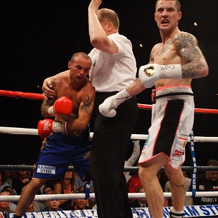The referee stops the fight as victor Ricky Burns, right, wheels away in delight