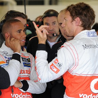Lewis Hamilton, left, and Jenson Button talk in the pits