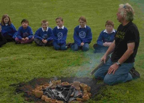 Julian Richards baking the children's clay pots in a fire pit.