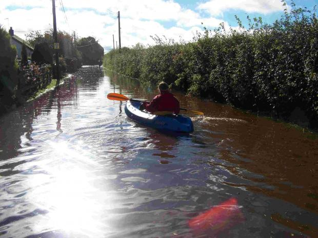 A canoeist makes his way down the road in Stuckton.