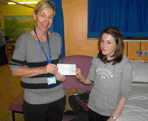 Beth Adams hands over a cheque for £250 to Dr Alice Lehey, consultant pediatric rheumatologist at Southempton General Hospital.
