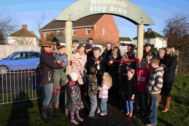 Councillor Lucy Clark, chairman of East Dorset District Council, cuts the ribbon to open the new play area at Woodlands along with representatives of Knowlton Parish Council, Synergy's Zone 10 Panel and members of the community.