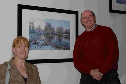 Associate director at Smith & Williamson Brigitte Potts and Iain Laing with one of his photographs.