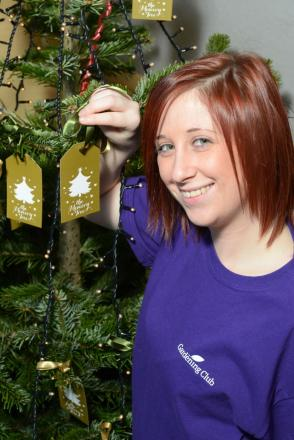 Holly Marshfield, Garden Centre Assistant, putting her memory on the tree to raise money for the Alzheimer's Society at Country Gardens Salisbury.