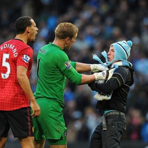 Manchester City goalkeeper Joe Hart holds back Matthew Stott as he approaches Manchester United's Rio Ferdinand