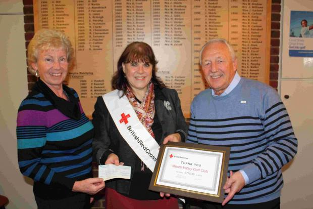 Moors Valley Golf Club's past club captain Alan Excell and past ladies captain Liz Dicker present a cheque for £775.56 to Jan Treacher-Evans a senior fundraiser for The British Red Cross.