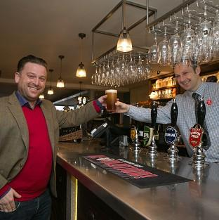 Salisbury Journal: Tom from Beaconsfield, left, buys the first pint from shift manager Derek at the new JD Wetherspoon pub called Hope And Champion at the M40 services at Beaconsfield