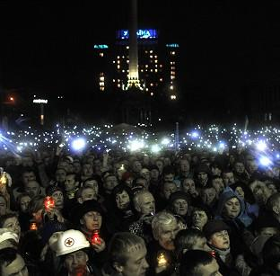 Salisbury Journal: People turn on mobile phones and flash lights as a body of an anti-government protester killed in clashes with police is brought to Independence Square in Kiev, Ukraine (AP)
