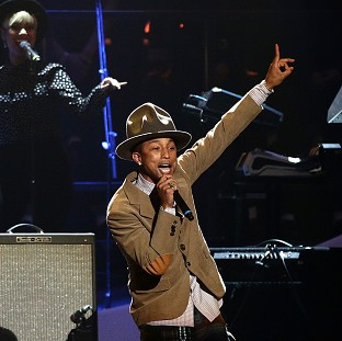 Pharrell Williams' hit Happy has hit the top of the singles chart for a third time - the first track to do this for 57 years