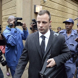 Oscar Pistorius is escorted outside court during a recess (AP)