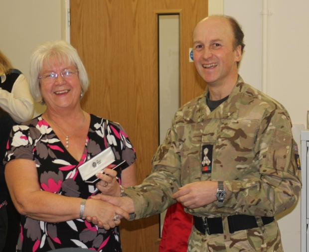 Marion Wardell is presented with her medal by Brigadier Piers Hankinson