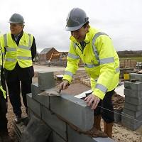 Salisbury Journal: George Osborne lays a block during a visit to a building site in Nuneaton, the day after he said the Government would extend the equity loan portion of Help to Buy