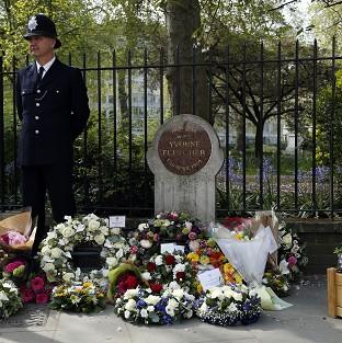 Salisbury Journal: A police officer stands beside floral tributes during a memorial service held in St James Square, London, to mark the thirtieth anniversary of the death of WPC Yvonne Fletcher