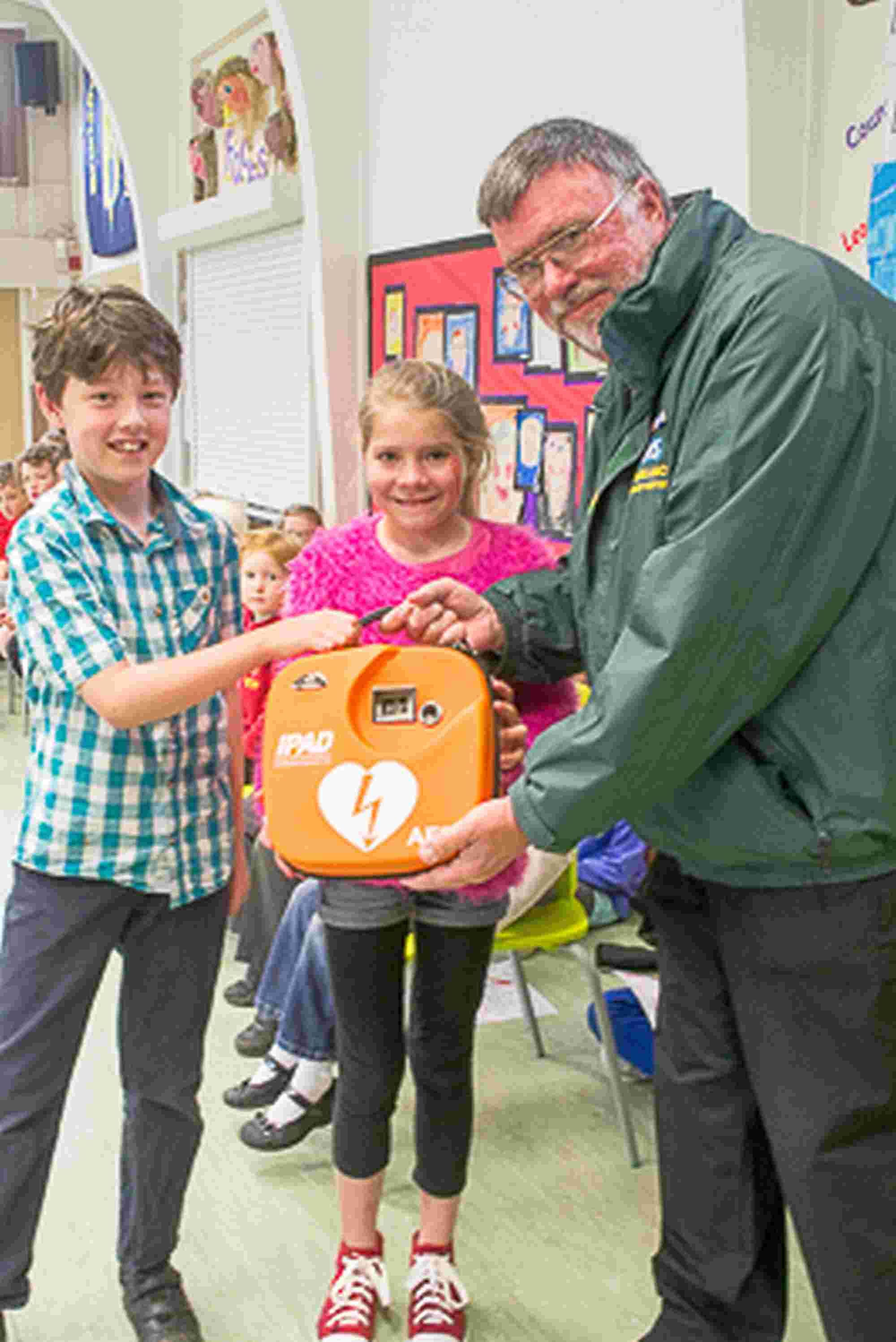 Mike Jukes from the Bransgore Community First Responders hands over the defibrillator to Bransgore Primary School pupils Wilf Jenkinson and Alice Waite. Picture: Mopho Photography