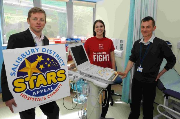 Dave Cates from the Stars Appeal and Alison Rosier from the British Heart Foundation present the equipment to Dr Nick Brown