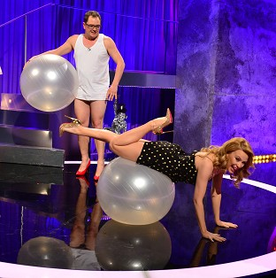 Kylie shows Chatty Man host Alan Carr how to roll on an exercise ball (Open Mike)