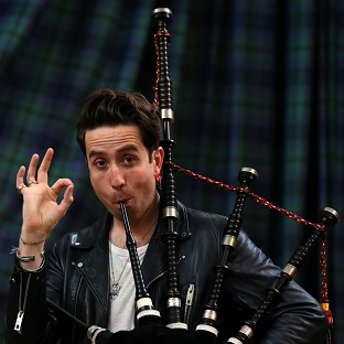 Radio 1 breakfast show host Nick Grimshaw is taught how to play the bagpipes at The National Piping Centre in Glasgow by Finlay MacDonald ahead