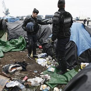 Salisbury Journal: Police officers take positions in a makeshift camp housing hundreds of illegal migrants from Syria, Afghanistan and Africa, after French authorities started to clear out camps in Calais