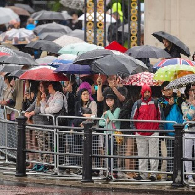 Salisbury Journal: Spectators sheltering from heavy rain as they watched the final rehearsal of Trooping the Colour