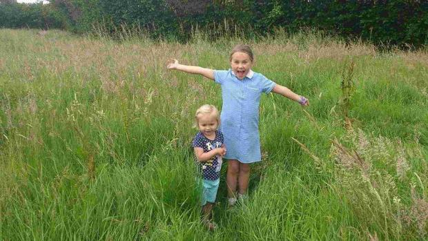 Charlotte Geary, two, and her sister Ellie, seven, demonstrate how high the grass is at Ebblake