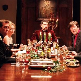 Rowan Atkinson as Lord Edmund Blackadder (centre) entertains his friends at a New Year's Eve dinner at Blackadder Hall
