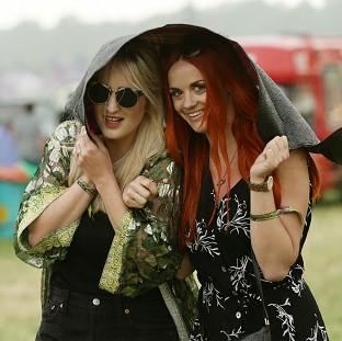 Salisbury Journal: Festival goers during a rain shower at the Glastonbury Festival, at Worthy Farm in Somerset