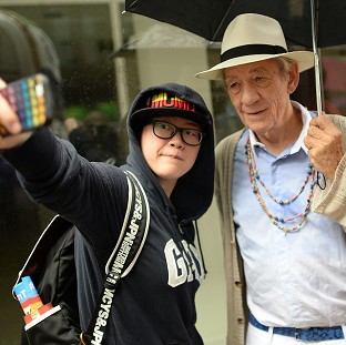 Sir Ian McKellan poses for a selfie with a reveller at the Pride in London Parade