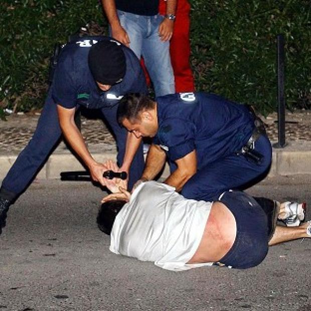 Salisbury Journal: Portuguese police restrain a fan during disturbances at Albufeira on the Algarve during Euro 2004