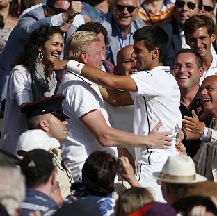 Novak Djokovic hugs Boris Becker, left, following his Wimbledon win