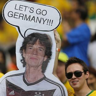 Brazil fans hold a poster depicting Rolling Stones singer Sir Mick Jagger wearing a Germany shirt be