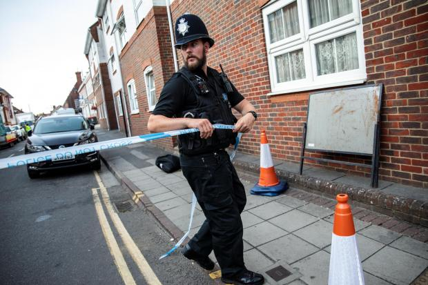 Salisbury Journal: SALISBURY, ENGLAND - JULY 05: A police officer fixes police tape across a street by a supported housing project in Salisbury after a major incident was declared when a man and woman were exposed to the Novichok nerve agent on July 5, 2018 in Salisbury, En