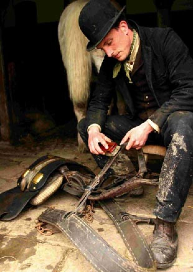 Alex Langlands, from BBC's Victorian Farm, cleaning the shire horse leathers. Copyright Lion Television Ltd 2009