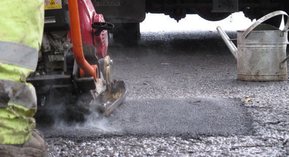 A CEC highways worker repairing a pothole